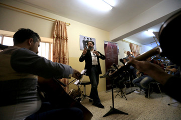 Conductor Karim Wasfi trains the musicians on musical tracks in Mosul