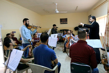 Karim Wasfi, conductor of the Peace Through Arts Farabi Orchestra, trains the musicians on musical tracks in Mosul