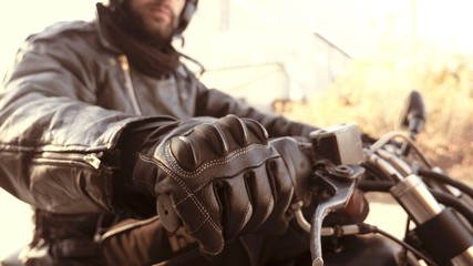 Motorbike person in leather gloves on start handle ready to go
