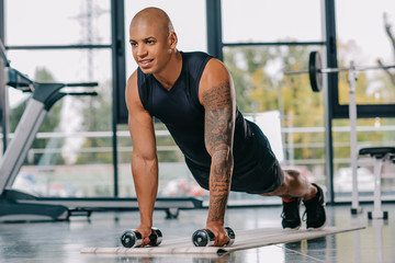 handsome african american sportsman with tattooed hand doing push ups with dumbbells on fitness mat at gym