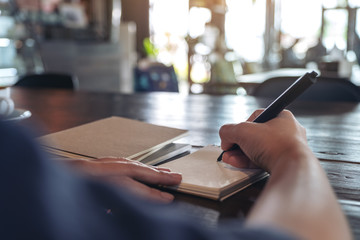 Closeup image of a woman writing on blank notebook on table in cafe