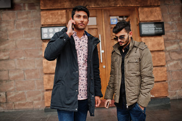Two indian guys on jackets posed outdoor against door of pub.