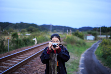 Young woman pointing camera between railroad tracks and narrow country road