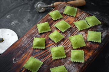 uncooked green organic ravioli pasta with spinach handmade on kitchen table