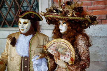 Carnival pair brown-gold mask and costume at the traditional festival in Venice, Italy