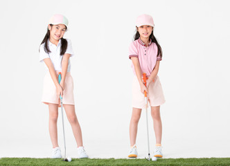Brother and sister Asian in sportswear and colorful hats are happy with pose the way they play golf on astroturf isolated on white background