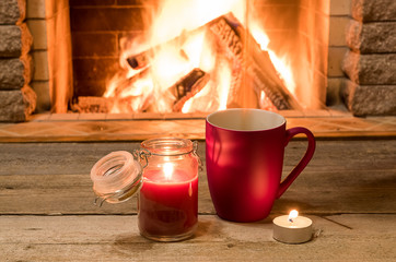 Cozy scene near fireplace with a Red cup with hot tea and candles.