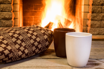 Cozy scene near fireplace with two cups of hot tea and cozy warm scarf.