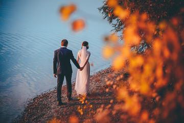 Wedding couple, autumn evening by lake