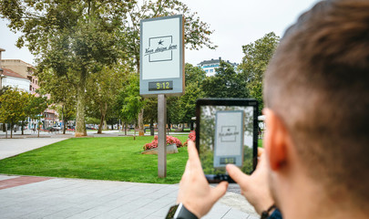 Young man taking photo with the tablet to customizable advertising poster. Selective focus on poster in background
