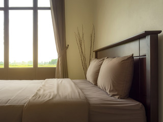 Empty double wooden bed on side of large windows with morning sunlight in luxury and natural style bedroom is simple decorated with two pillow.