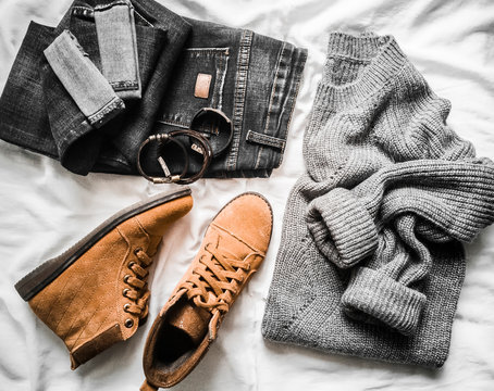 Set of women's autumn, winter clothes on a light background - jeans, gray pullover oversize, suede brown boots and scarf. Fashionable clothes for walks, flat lay