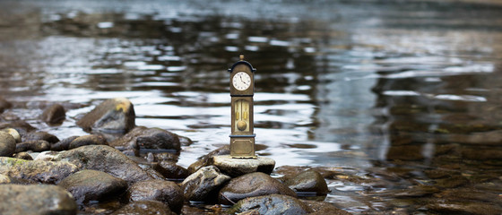 Vintage antique standing clock by the riverside