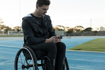 Disabled athletic using mobile phone at sports venue