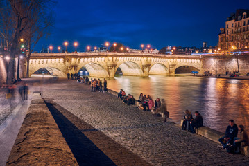 People rest on the banks of the Seine river in Paris  Wall mural