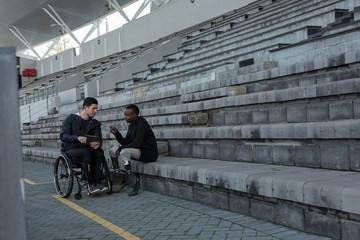 Two disabled athletics discussing over digital tablet