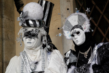 Carnival pair black-white-silver mask and costume at the traditional festival in Venice, Italy