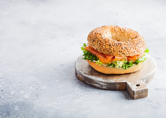 Photo sur Plexiglas Snack Fresh healthy bagel sandwich with salmon, ricotta and lettuce on vintage chopping board on stone kitchen table background. Healthy diet food. Space for text