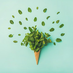 Flat-lay of waffle sweet cone with fresh mint over light blue pastel background, top view, horizontal composition. Spring or summer mood concept, square crop