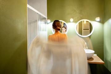 Beautiful loft interior bathroom with motion blurred woman wearing bathrobe