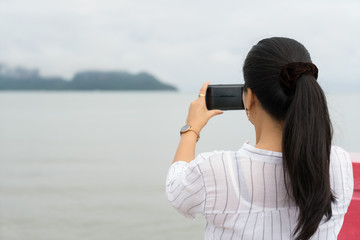 woman is standing taking photo with smartphone of  with fog on Khao Ta Mong Lai Forest Park background, Thailand