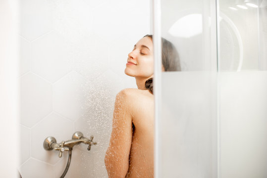 Young and beautiful woman washing her face, taking a shower in the white cabin