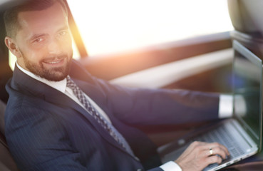 Confident businessman with laptop sitting in auto.