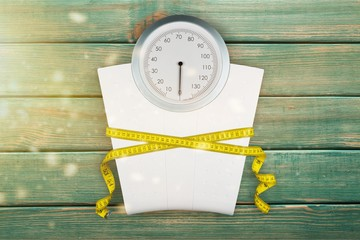 Bathroom scale with a measuring tape on background