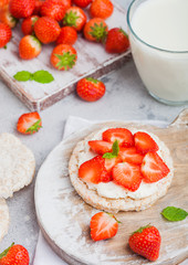 Healthy organic rice cakes with ricotta and fresh strawberries on wooden board and glass of milk on light stone kitchen background. Top view.