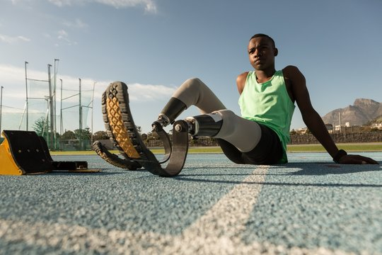 Disabled young athlete relaxing on running track
