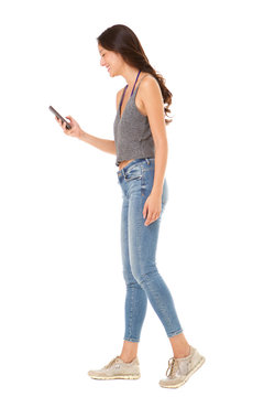 Full body side portrait of young asian woman looking at mobile phone