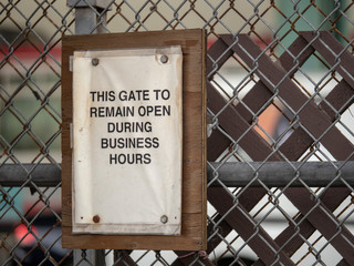 This gate to remain open during business hours paper sign on fence