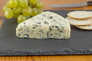 Blue cheese wedge on slate board close up with defocused green grapes and crackers in background