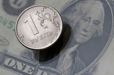 A view shows a Russian rouble coin and a U.S. dollar banknote in this picture illustration