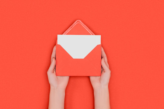 partial top view of person holding red envelope with blank white card isolated on red