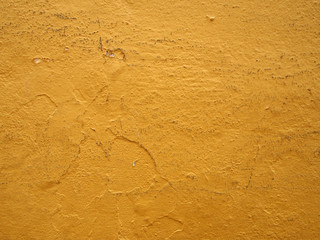 Bright yellow dirty painted cracked old wall texture background