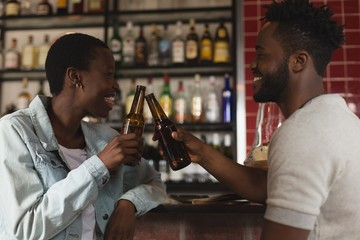 Couple toasting beer bottle in cafe