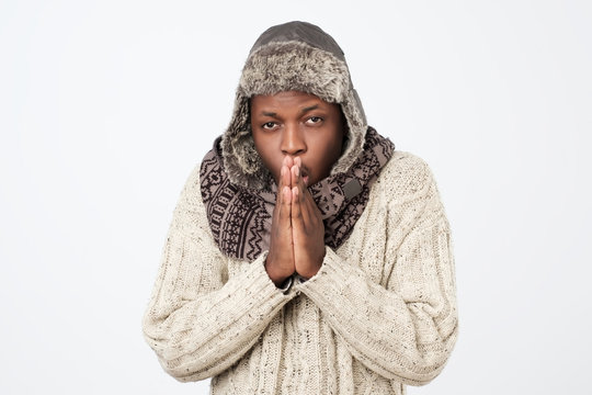 African American man wearing winter clothing but feeling cold in a white background