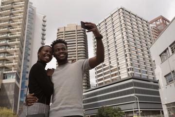 Couple taking selfie on city street