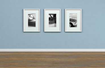 A sequence of three framed hanging pictures on a flat blue wall in a house with shiny wooden floors - 3D render