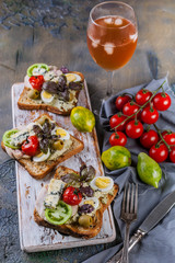 Appetizing toasts with avocado, quail eggs, tomatoes, Dor Blue cheese and a glass of cold white wine. Author's cuisine. Original serving dishes
