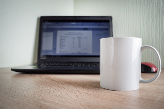 White mug is on the table in front of the laptop