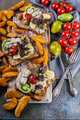 Appetizing toasts with avocado, quail eggs, tomatoes, Dor Blue cheese and french fries. Author's cuisine. Original serving dishes