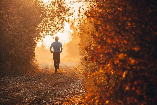 Man train in orange and red autumn nature. Sport photo