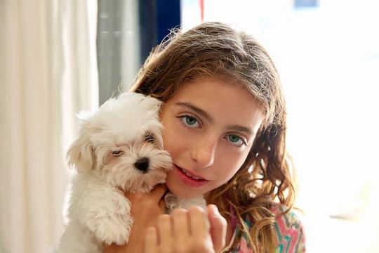 Kid girl with puppy white dog maltichon