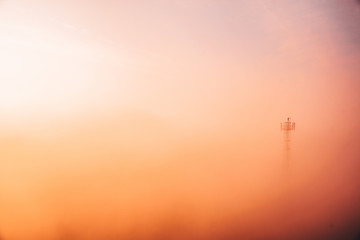Man at the top of tower in colorful morning mist