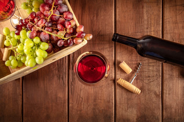 Cellar Tasting. A photo of wine glasses with a bottle, red and green grapes, a vintage corkscew and a cork, shot from above on a dark rustic wooden background with a place for text