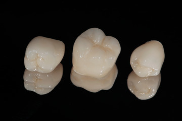 Ceramic dental crowns on the mirror, chewing teeth