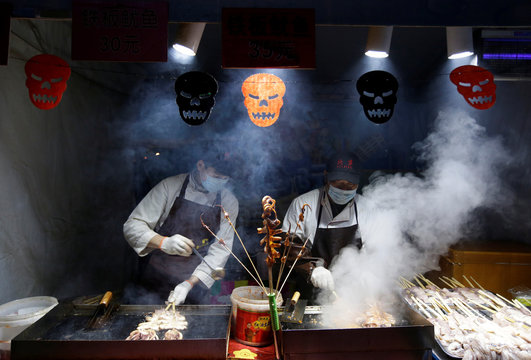 Cooks make grilled squid during a Halloween event at Happy Valley park in Beijing,