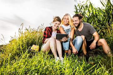 Friends sharing tablet at a cornfield